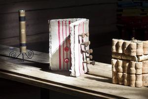 En bokrygg, en skruvad bok och en korkad bok.