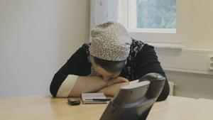 Aina väntar på en telefontolkad förhandling med polismyndigheten, efter att ha suttit inlåst sex månader. Ur dokumentärfilmen