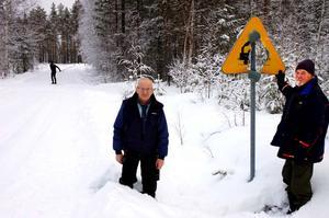 Anders Andersson och Mats Eriksson vid skylten som ska varna för järnvägskorsningen. Bakom dem passerar Vasaloppspåret vägen.