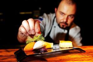 Köksmästaren Radek Jackiewicz på restaurang Invito, färdigställer en förrätt med Kalixlöjrom.