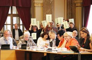 Flera åhörare stod upp i en tyst protest mot försäljningarna av lägenheter. I mitten stod vänsterpartisten Mario Izquierdo.