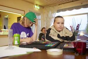 Nioårige Gustav Johansson och åttaårige Linus Fredriksson-Söderlund trivs på Fritidsgården. Här ses de vid ritpennorna, men även bordtennisen lockar.