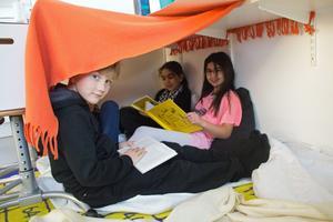 Ossian Friman, Hevin Said och Marya Elturk läser i den specialbyggda läskojan.