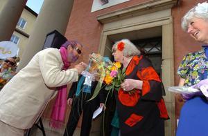 Anita Blomqvist (S), ordförande i kommunens kultur- och fritidsutskott, får en kyss på handen av Frank Larsen.