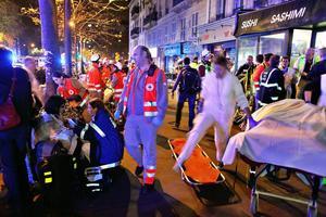 Skadade och chockade människor hjälps ut från Bataclan. Minst 120 människor har dödats i attacker på sex olika platser i Paris.