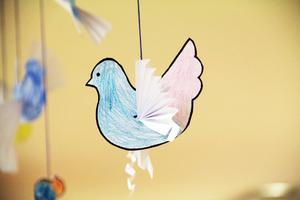Ovanför bänkarna flyger vackra pappersfåglar, som barnen har gjort.