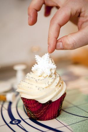 Vintervacker. Grädde med smält marshmallow, små små silverpärlor, pärlemorsprej och en snöflinga i sockermassa toppar denna cupcake.