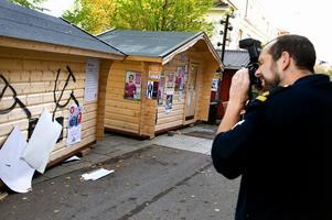 Vänsterns valstuga sprejades och rutan krossades. Brottsplatsundersökare Roger Andersson, polisen i Borlänge, dokumenterar skadegörelsen. Foto:Johan Larsson