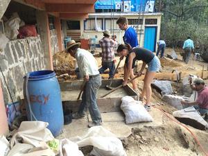 Simon  Alzèn hjälper till att bygga skola i Guatemala. Volontärerna bygger i åtta timmar om dagen. Väggarna fylls med petflaskor som sedan täcks med cement.