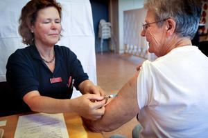 Distriktssköterska Ingrid Stålberg ger Anna Bolinder en spruta med vaccin mot svininfluensan. Om några veckor är det dags för dos två.