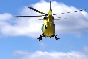 Helikoptern for iväg mot den blåa himlen.
