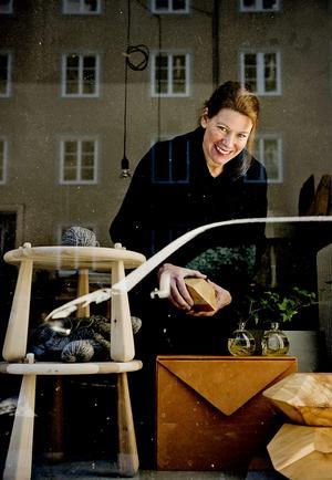 """Prototypen till det skinnklädda skåpet """"Brev"""", som Emma Olbers designat, står i fönstret på kontoret. I handen håller hon en av träskulpturerna från serien """"Stockholm Wood""""."""