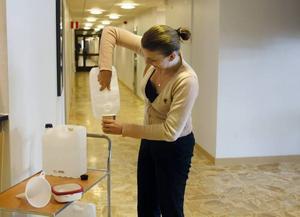 Belma Tabak fyller på vatten till sin lunch. Anna Larsson och Linda Persson som jobbar i receptionen intill vattendunkarna berättar att de själva hållit sig till Ramlösa och Statoilkaffe under förmiddagen.