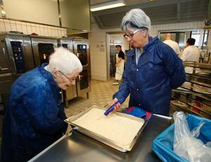 Birgitta Månsson tar temperaturen på riset. Ulla Linberg är intresserad av nymodigheterna inom matlagningen.