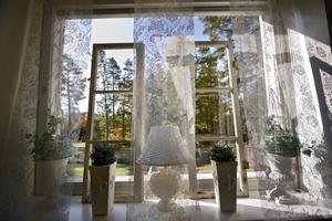 De stora perspektivfönstren har Annica liksom mjukat upp med hjälp av spetsgardiner och gamla fönsterbågar.