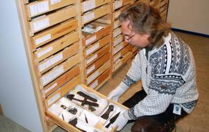 Förste antikvarie Anders Hansson visar mässingsbeslag, yxa, kniv och mässingskedja som fanns i graven jämte skelettet.