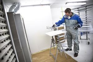Lackering av skåpluckor är en verksamhet som växer. Det är Stefan Hedkvist som håller i sprutaggregatet.