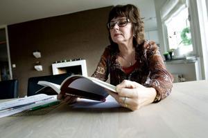 Rose-Marie Bergmark bläddrar i den nya bok om kroniskt trötthetssyndrom som hon varit med och skrivit.