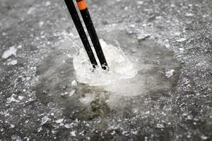 Slå på isen för att testa bärigheten.