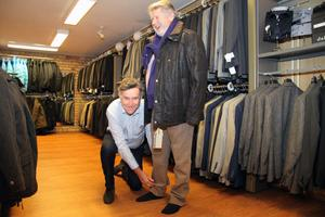 Butiksägaren Tomas Andersson ser gladeligen till att den minst lika glada mannekängen Sten Sundfors får rätt längd på byxorna till höstmodevisningen.