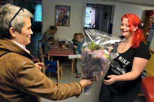Karin Adolfsson från kultur- och bildningsförvaltningen ger blommorna till Emma Edman.