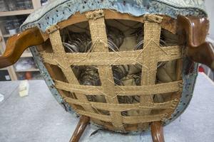 På undersidan av Emma-fåtöljen ser man vilket hantverk den är. Sitsen har bland annat formats med handspunna fjädrar, intrikat knutna snören, juteväv och handvävd sadelgjord.