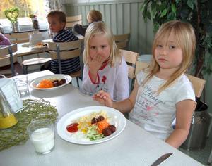 Felicia Olsson-Gustafsson och Engla Dahlén har komponerat varsin tallrik köttbullar, makaroner och grönsaker.