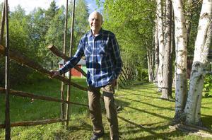 Ivan Lunnehed trivs bäst i stugan vid Stortjärn i Långå där han och barnbarnet Micke håller på att sätta upp hage runt tomten.