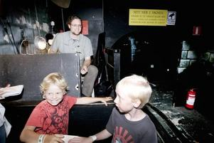 Anders Thelin sommarjobbar som karusellskötare i spökborgen på Furuviks tivoli. Joakim Larsson och Melker Sahlin åker varv efter varv i spökvagnarna.