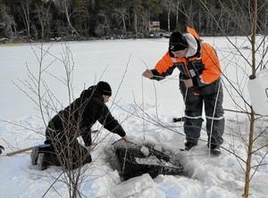 Isfiske. Hampus Andersson och Jim Mannfolk firar upp mörtstugan ur sin isvak.