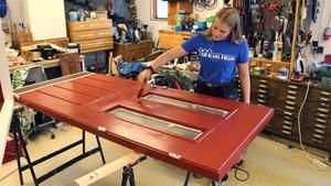 Lina målar dörren i morfars verkstad där hon också kunnat låna verktyg.