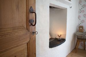 Även i sovrummet finns en gammal öppen spis. Väggen i övrigt var täckt av en spånskiva. Den har Maria och Jonas tagit bort och istället har de låtit putsa hela väggen.