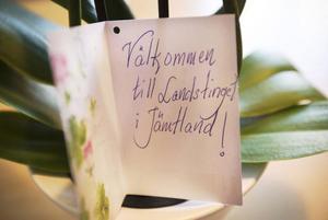 På bordet i tjänsterummet står en blomma med ett välkomstkort.