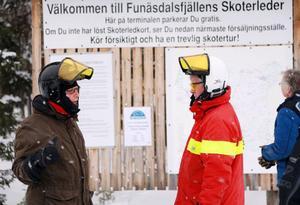 Ledvärden Kalle Arnell visar Anders Åkesson en av uppställningsplatserna och informationstavlan efter det 45 mil långa skoterledsystemet i Funäsdalen.