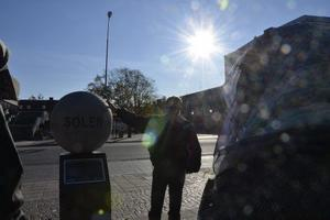 Solig start. På Olof Palmes torg, vid solmonumentet börjar vandringen med Kjell Olauson.