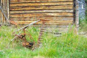 Den gamla slåttermaskinen, för en hästkraft, står kvar utanför den loge, där resultatet av dess möda förr lagrades. Den har nu vuxit fast i den mylla där den förut tjänstgjorde.