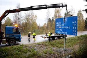Här lyfts en ny riksväg 66-skylt på plats strax norr om Hammarbacken i Ludvika.