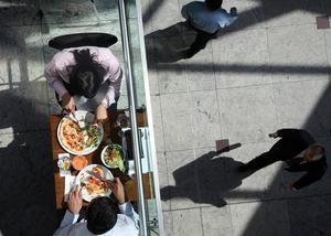 Två matgäster i ett litet hörn av den stora gallerian i finanskvarteren i Canary Wharf. Hela området som ser ut som en offentliga plats är privatägt. Det innebär bland annat att privata vakter beslutar vilka personer som får lov att fotografera och vilka som inte får det.