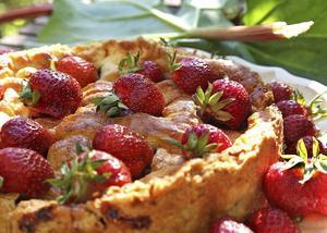 En välmatad rabarberpaj serverad med solmogna jordgubbar sticker ut på midsommarbordet. Rabarberns syra och jordgubbarnas sötma trivs bra tillsammans.