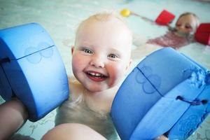 Malin Olsson, ett år gammal, är minst sagt nöjd med att få plaska i den varma barnbasängen.