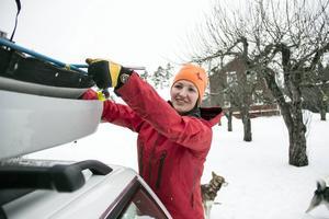 Karin packar bilen hemma på gården.