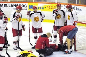 Oroliga Moraspelare följer Moras medicinska team när de tar hand om målvakten Ervins Mustokovs.