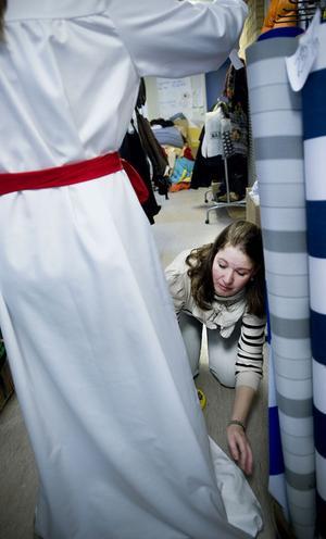 Birgitta Abrahamsson fixar rätt längd på klänningarna hon sytt.