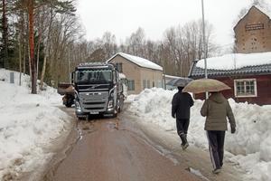 I regn och rusk kör lastbilarna i skytteltrafik  med fyllnadsmasor som ska förstärka skyddsvallen.