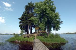 Den gula stugan ligger gömd bakom tallarna på båtklubbens ö.