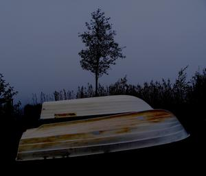 Skymningen faller  vid sjön och dimman tätnar bakom båtarna som är upptagna inför vintern.