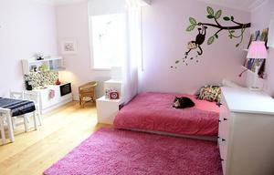 Stella har ett lekfullt barnrum med kökshörna, roliga väggdekaler och en mysig säng.