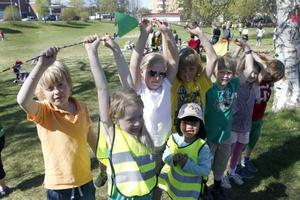 Barn från Stenhamreskolans fritids håller upp vänskapsbandet som de knöt ihop när Fritidshemmens dag invigdes i Jonsparken i Ljusdal.