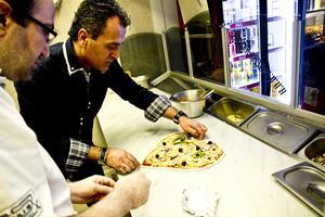 har den rätta knycken. Med ett bestämt ryck gör Senay Ucar om den runda pizzan till att bli hjärtformad. Pizzabagaren Bilal Öven studerar för att få in rätt teknik.