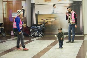 Ett flyktingbarn leker tafatt med en frivillig från en hjälporganisation på Stockholms central.